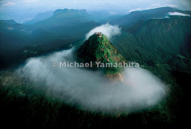 The sacred mountain, Adam's Peak, rises through the mist above Sri Lanka.