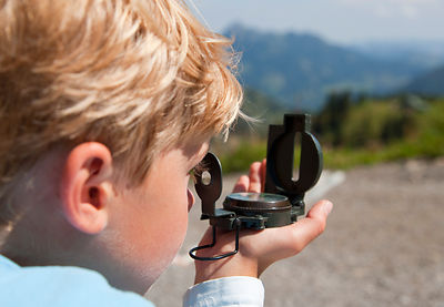 Boy using compass outdoors