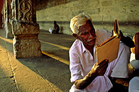India - Madurai - A man reads a religious book at the Sri Meenakshi Temple