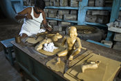 India - Swamimalai - A craftsman carves an icon from wax in the workshops of the Stpathy family of bronze statue makers