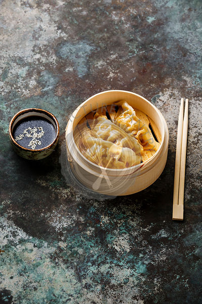 Steamed dumplings Gyoza in bamboo steamer with chopsticks and sauce on metal background copy space