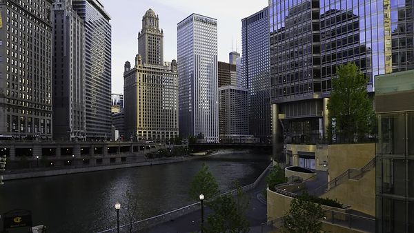 Medium Shot: Shadows Dance On High-Rises Over A Busy Chicago River (Day To Night)