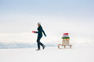 Woman pulls Christmas presents on sled