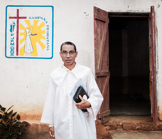 "MAHATSINJO - Mr Samson, married, 3 children, is pastor of the Protestant FJKM church at Toby Karmela. A ""toby"" (which can be translated as ""camp"") is a kind of dispensary run by ""Mpiandry"" (healer-exorcist) and which welcomes all sick people in need of care. I note that the majority of patients suffer from psychological disorders (depression, dementia, neurosis, psychosis, etc.). But here they are considered possessed by the devil or an evil spirit. Two or three times a week, at nightfall, the mpiandry of the Karmela toby gather the patients in the prayer room and, in the light of a small bulb, they proceed to a collective exorcism session. The patients pass in turn in front of a mpiandry, who pronounce incantations and prayers, a bible in his hand, to cast out evil eye, evil spirits, demons, or simply to psychologically prepare a fragile person not to be invaded by evil spirits. These sessions last between two and three hours. The mpiandry focus a lot on certain people, like this 13 year old girl, considered as affected by a particularly ""tough"" demon. They are two mpiandry ""working"" on her for over an hour. The strident screams of the young girl, in a state of insanity and at the end of nerve, mix with the aggressive psalmodies of the mpiandry plunging the rest of the audience into a form of collective trans."