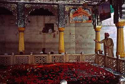 India - Delhi - A man sprinkles petals over the shrine of the Sufi Saint, Bakhtiar Kaki in Mehrauli