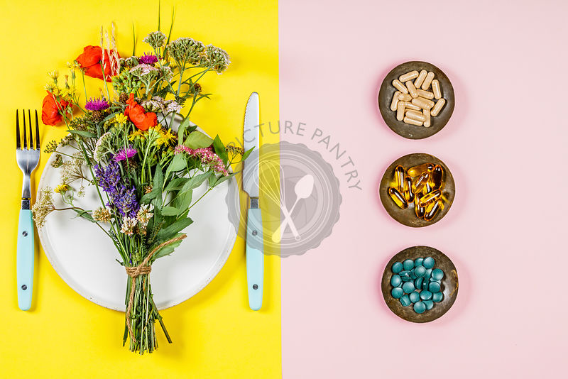 Flat lay of wild flower bouquet on white plate and herbal capsules. Clean eating, paleo, biohacking, herbal medicine concept