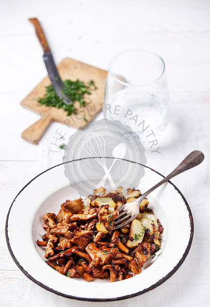 Fried chanterelles with potatoes and onion in a bowl on the table