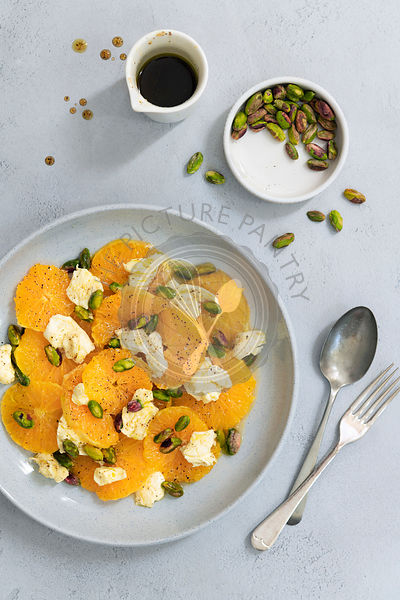 Freshly sliced oranges with bocconcini pieces, pistachio nuts and a spicy dressing.