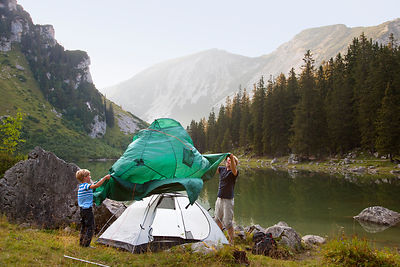 Father and son pitching a tent by lake
