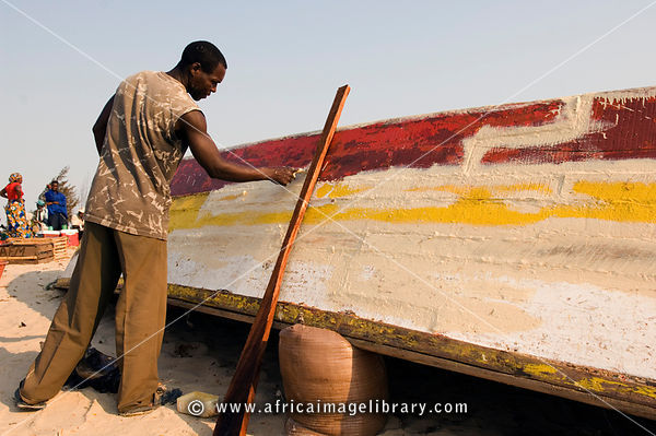 Mozambique, Beira, man painting and repairing fishing dhow.