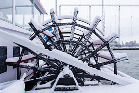Snow covered paddle wheel of a river boat at Chelsea Piers in New York on snowy day.