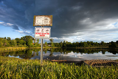 Sign with fishing and swimming regulations near a lake in Green Farm Park, Maryland