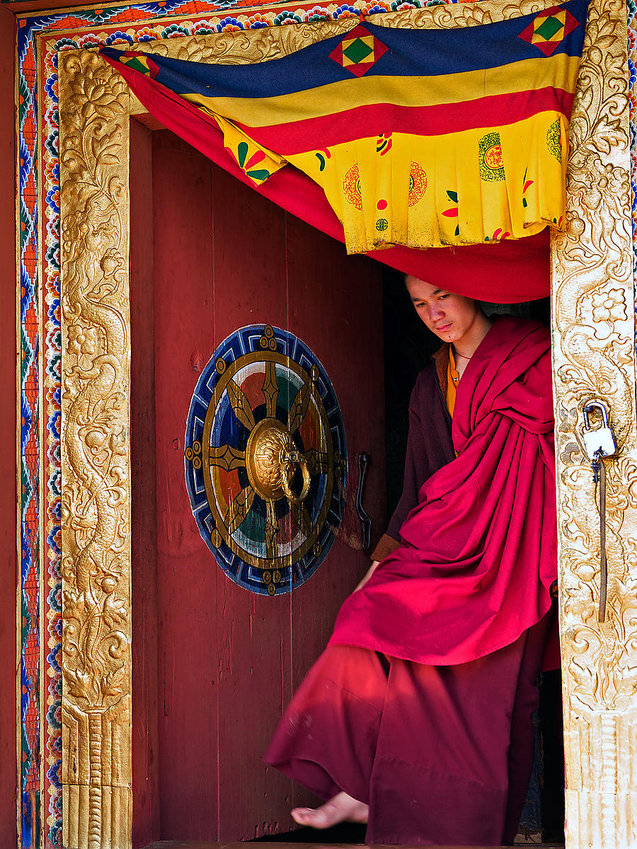 A young buddhist monk seems lost in his thoughts while he walks out of a door during the Thimphu festival, Bhutan.