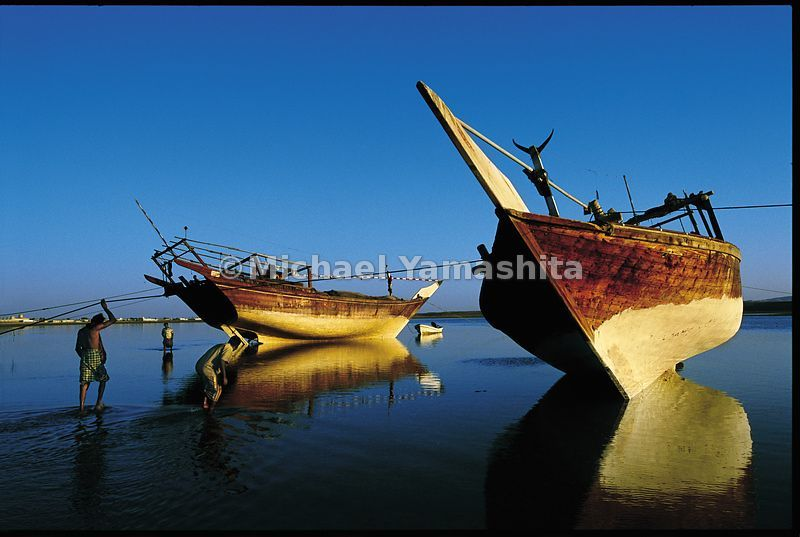 Fishermen, waiting for high tide, inspect the hulls of their wooden dhows.