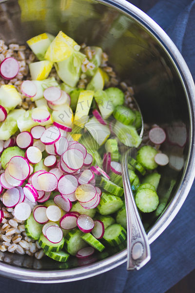 Farro salad with cucumber, radish and dill, being mixed in a mixing bowl.
