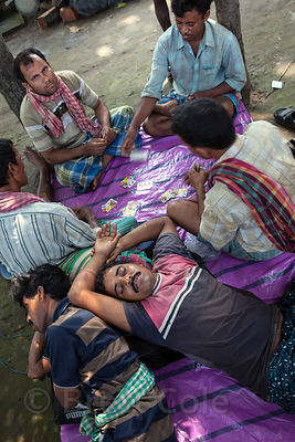 Men sleep and play cards near Sovabazar Ghat on the Hooghly River, Kolkata, India. Sleeping in public is very common in Kolkata.