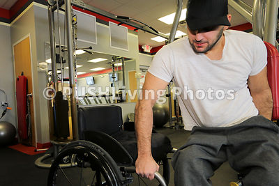 Man in a wheelchair working out at a gym