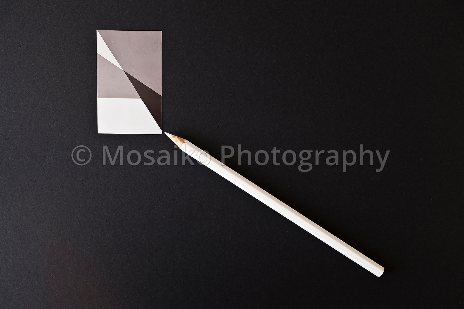 white pencil from above - black background