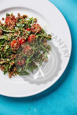 Salad with quinoa, tomato and arugula on white plate on blue background close-up