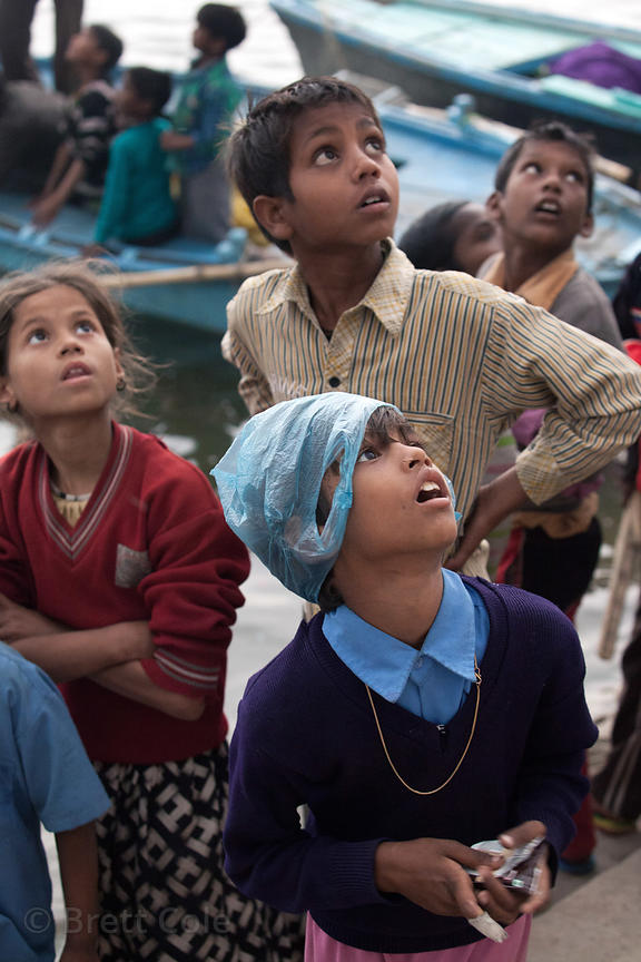 Children watch a kite near Assi Ghat, Varanasi, India.
