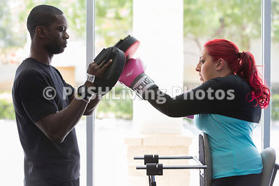 Disabled Woman Boxing With Personal Trainer