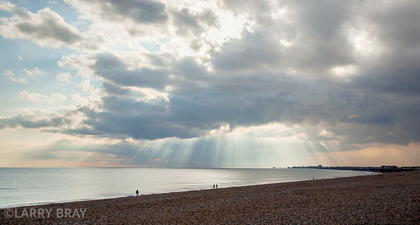 Rays of sun shining through the clouds over the beach in Shoreham-by-Sea, West Sussex, UK