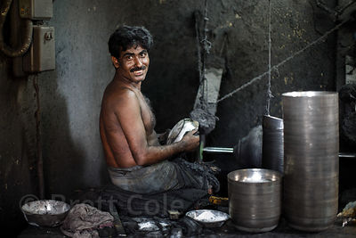A man works at a metal fabrication shop without any health precautions, Beniatola, Kolkata, India. Respiratory disease is a m...