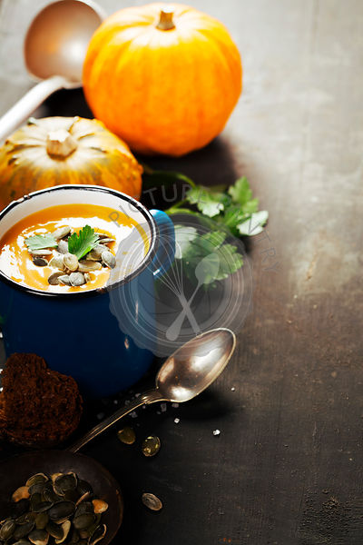 Pumpkin soup in a metal mug on a wooden surface