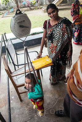 A baby is weighed at a clinic operated by Child in Need Institute (CINI, cinindia.org) in Pailan, Kolkata, India