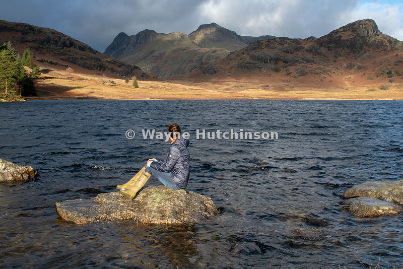 Woman sitting on a rock in Blea Tarn admiring the landscape which includes the Langdale Hills, Cumbria, UK.