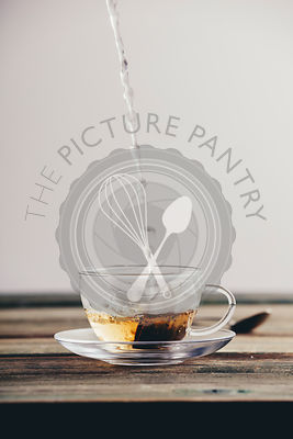 Pouring hot water into glass cup with tea bag on wooden table background