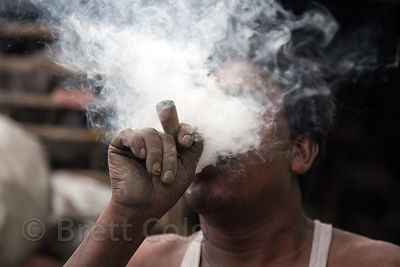 Recycling workers smoke a tobacco pipe, Dhapa, Kolkata, India