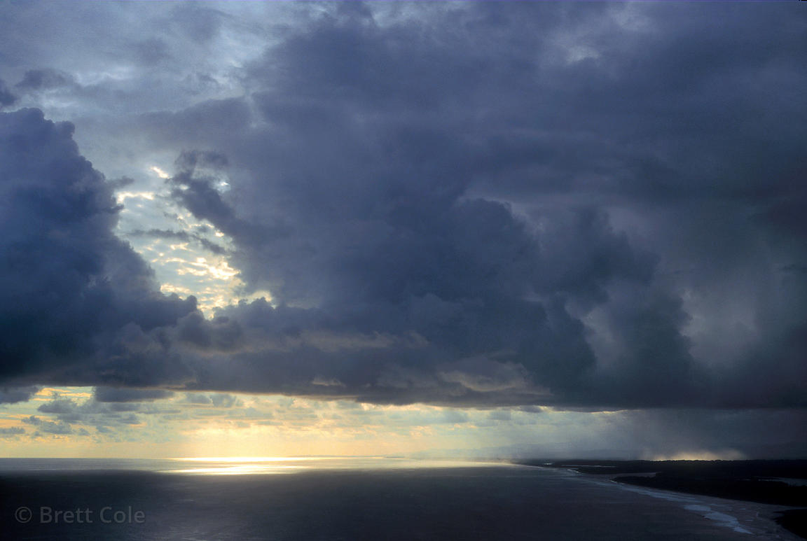 The sun shines through dramatic stormclouds onto the Pacific Ocean. Near Quepos, Costa Rica