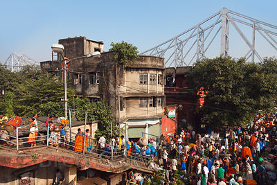 View of Howrah Bridge and the bustling Howrah flower market, Kolkata, India.