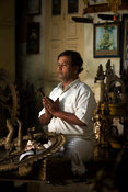India - Swamimalai - Master craftsman Radhakhrishna Stpathy, prays and offers a devotion at dawn before carving the eyes into...