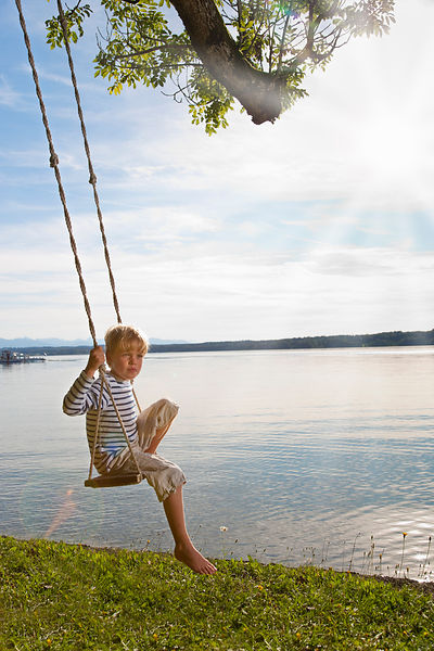 Boy swinging from tree by lake