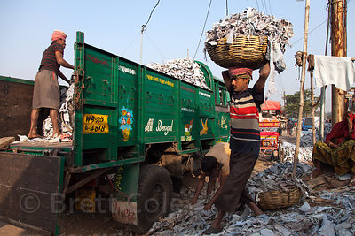 "A man loads leather scraps onto a truck in a ""slum"" in Chamrapatti, Kolkata, India. Leather tanning for handbags and purses i..."