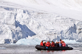 A group of polar explorers from the National Geographic Explorer cruise through the Hornsund fjord near a snowy glacier.