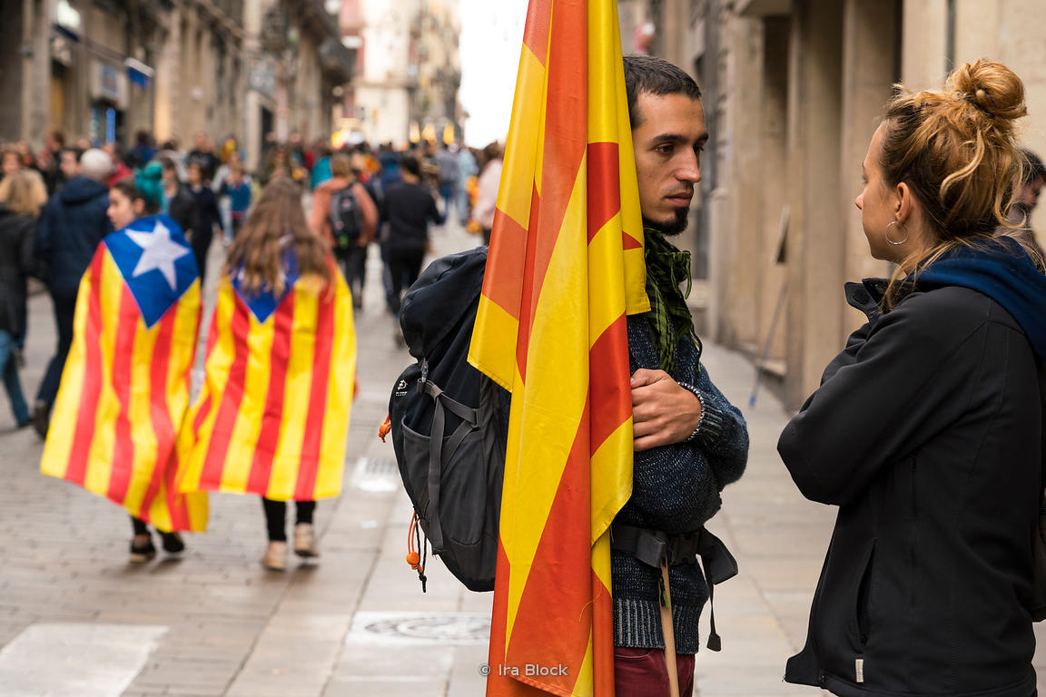 A protestor walks with the secession flag at the protests for Catalonia independence near Plaça Sant Jaume  in Barcelona, Spain
