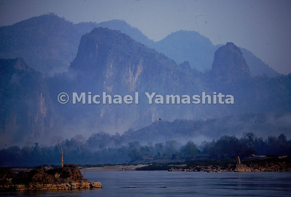 Mountains resembling a Sung dynasty watercolor loom above the Mekong as it flows through Pak Ou, Laos.