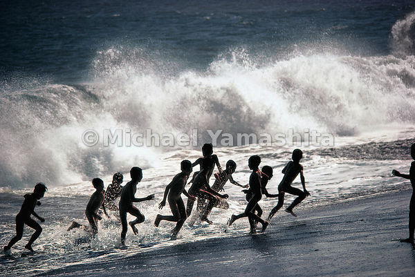 Children play in the surf on a Balinese beach.