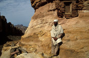 Priest standing at the entrance of Abuna Yemata Guh rock-hewn church in Gheralta, Ethiopia