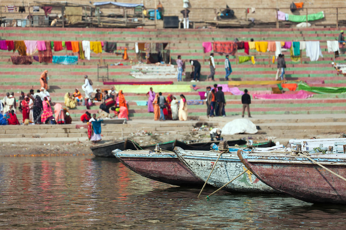 Women in saris bathe in the Ganges River near colorful drying laundry, near Ram Ghat, Varanasi, India.