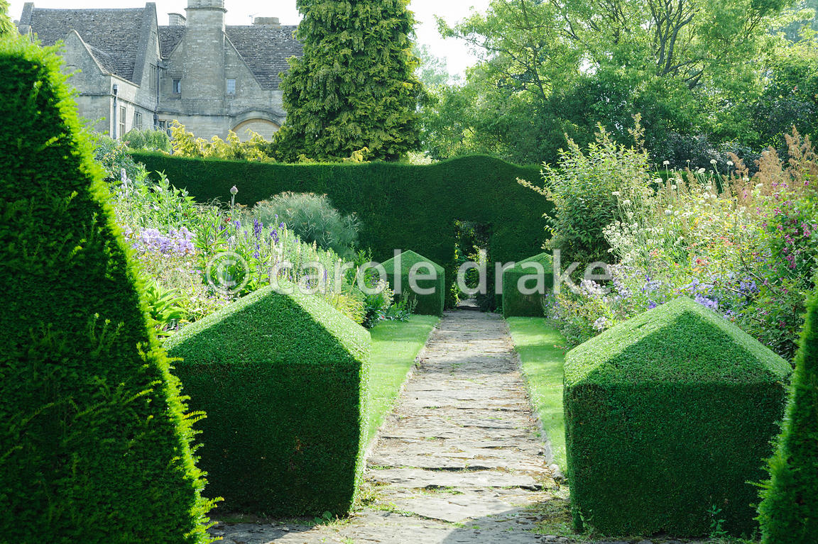 Double herbaceous borders framed with clipped box and tall yew hedges include delphiniums, phlox, campanulas and poppies. Rodmarton Manor, Rodmarton, Tetbury, Glos, UK