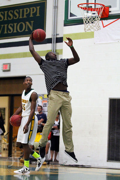 Iowa City West High's Dondre Alexander, who was not participating in the event, shows the crowd how he can dunk. The Northern...