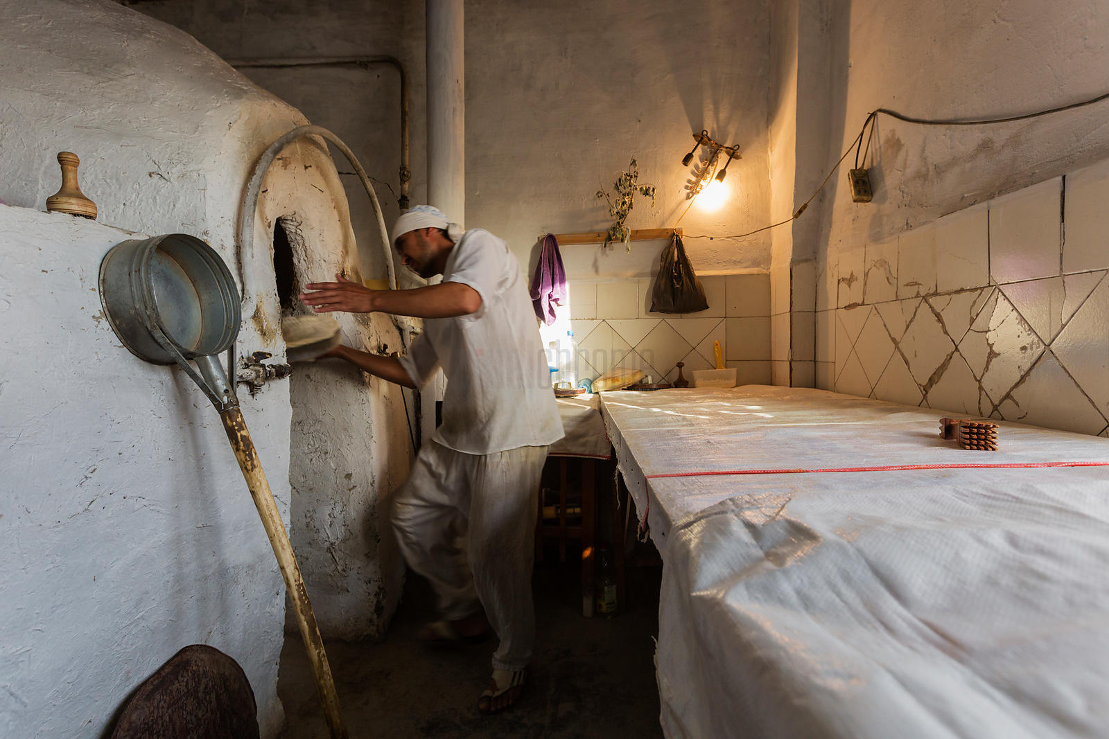 A Baker Places Bread Dough in the Tandoor Oven.