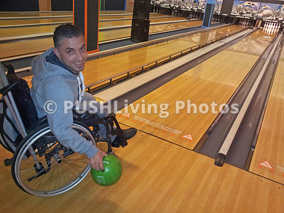 Young man in a wheelchair ten pin bowling