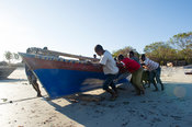 Fishermen pushing a dhow into the water, Kilwa Masoko, Tanzania