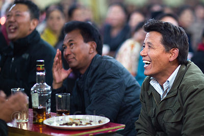 Guests laugh and drink at a wedding in Leh, Ladakh, India