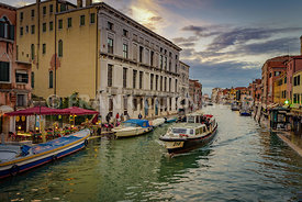 VENICE, ITALY - OCTOBER 31, 2018: A canal at dusk in Venice with restaurants and boat traffic.